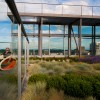 Woman relaxing on the Eco Roof atop Indigo @ 12 West Building, a LEED Platinum Building with green roof & wind turbines, Portland, OR